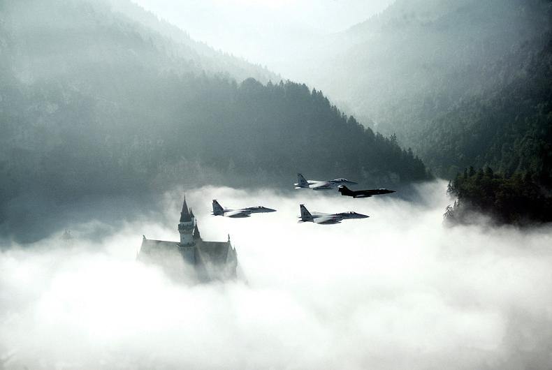 four fighter jets flying over castle
