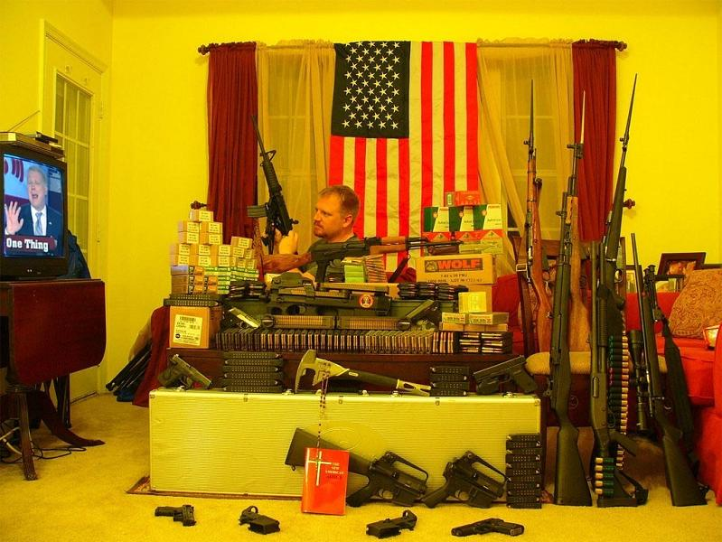 man in living room with lots of guns and american flag Picture of the Day   March 11, 2010