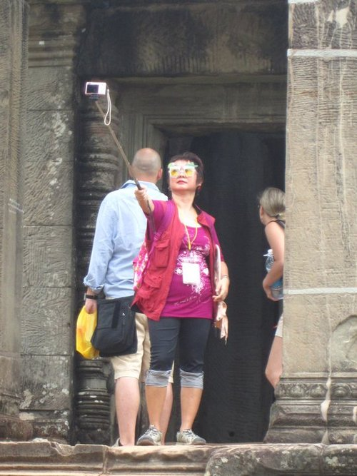 woman taking photo of herself with camera on a stick The Friday Shirk Report   November 12, 2010 | Volume 83