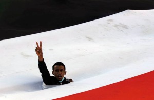 protests in yemen peace sign through flag 2011 Anti government protester flashes the victory sign as he emerges through a gap in Yemens national flag during a demonstration in Sanaa