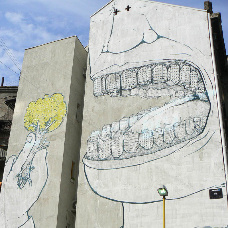 blu mural eating tree teeth made of buildings appetite for destruction Picture of the Day: Appetite for Destruction
