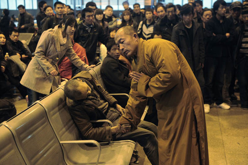 monk prays for dead person in airport china Picture of the Day: A Prayer for the Dead