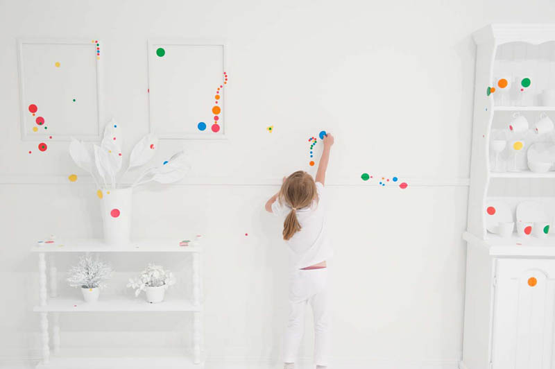 white room covered in stickers by kids yayoi kusama obliteration room 4 Kids Turn White Room into Explosion of Color