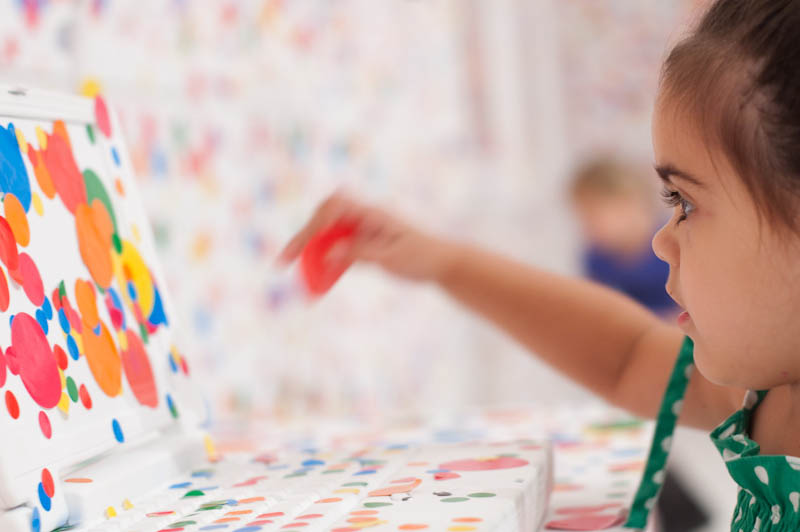 white room covered in stickers by kids yayoi kusama obliteration room 7 Kids Turn White Room into Explosion of Color