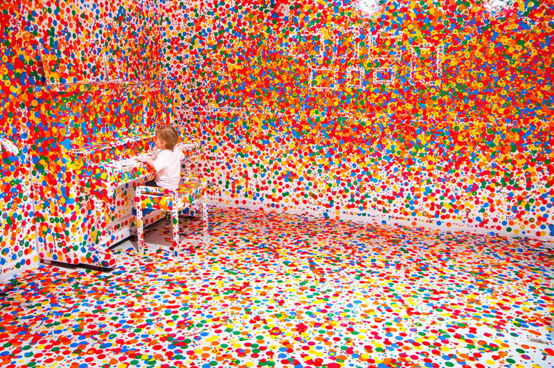white room covered in stickers by kids yayoi kusama obliteration room 9 Kids Turn White Room into Explosion of Color