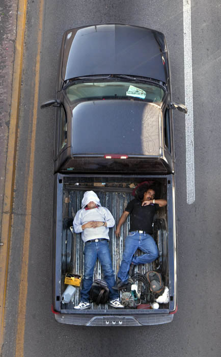 aerial birds eye view of people riding car pooling in back of pickup trucks from above alejandro cartagena 2 Riding in the Back of Pickup Trucks   A Birds Eye View