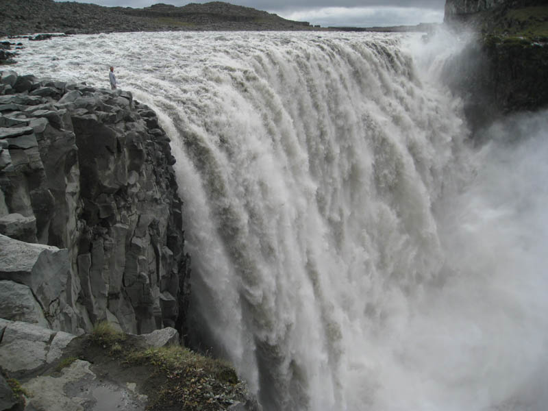 man standing next to Dettifoss waterfall in vatnajokull national park iceland the largest waterfall in europe