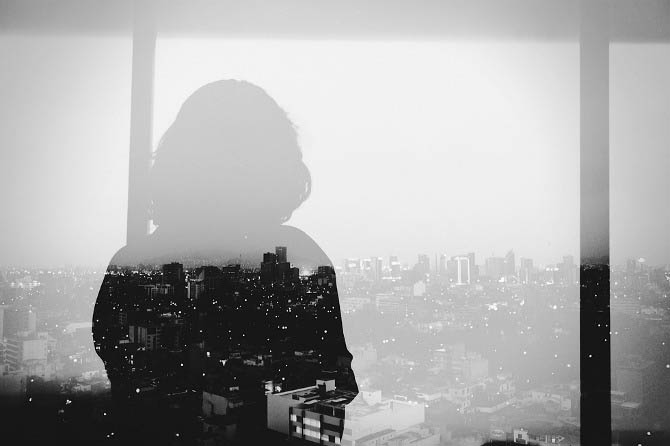 double exposure of woman looking out onto city from tall building