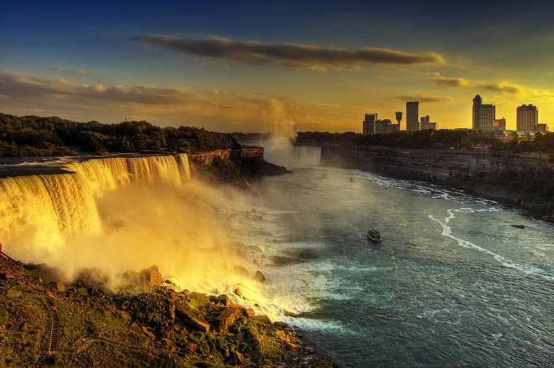 wide angle view of niagara falls with maid of the mist ship visible in the shot golden rays of sunshine on falls