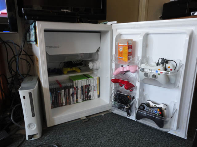 using old mini fridge as tv stand and storage unit