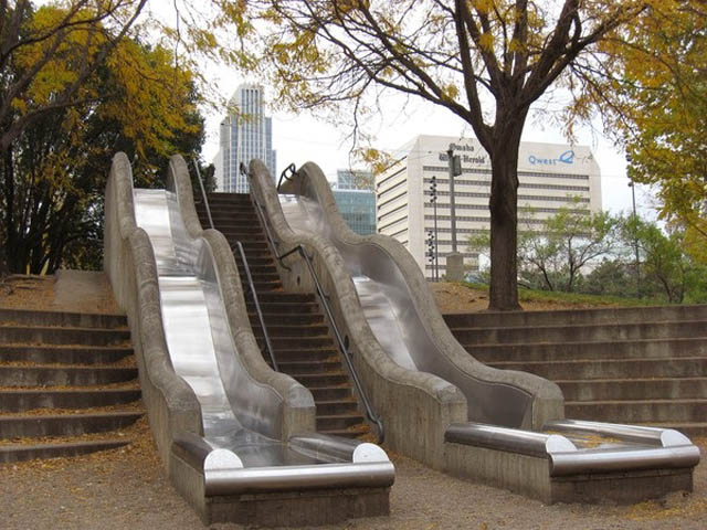outdoor staircase with metal slide right beside it