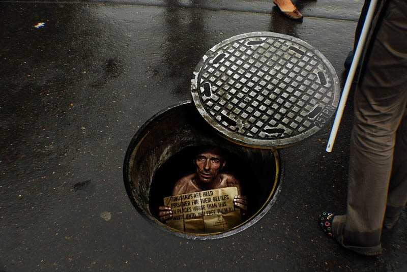 sidewalk sticker looks like a person is inside a manhole looking up at you in despair