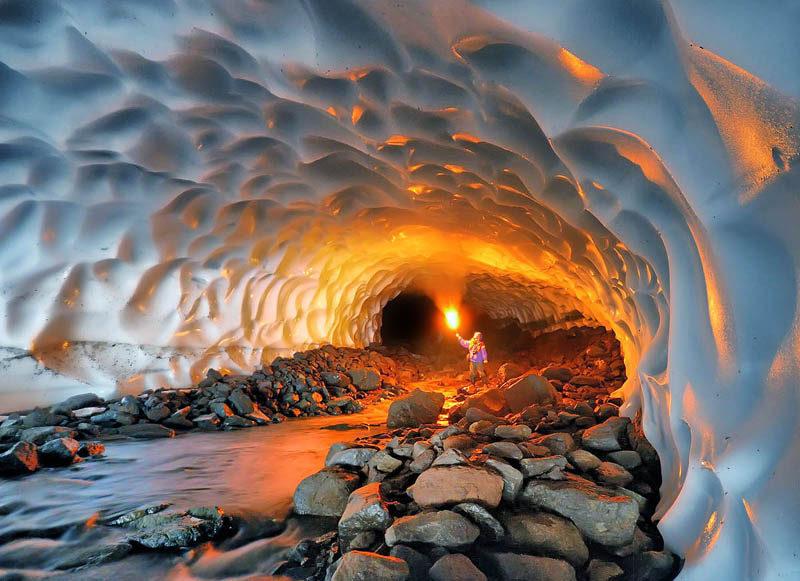 picture at the start of a 1km long snow tunnel with person facing camera lighting up the tunnel with a fire torch