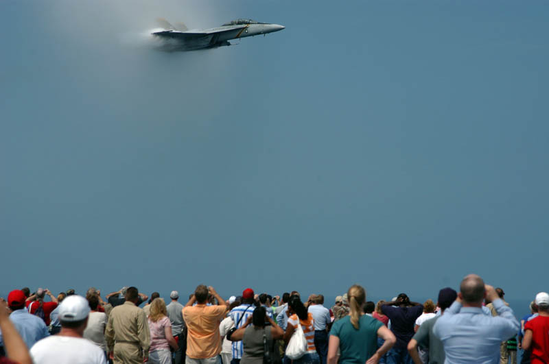 crowd of people watching a plane break the sound barrier