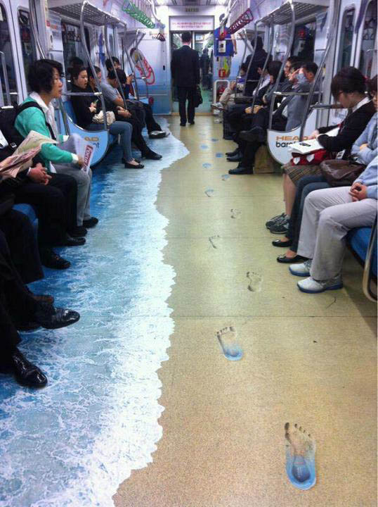 floor sticker decal on subway makes it look like a sandy beach with footprints and waves