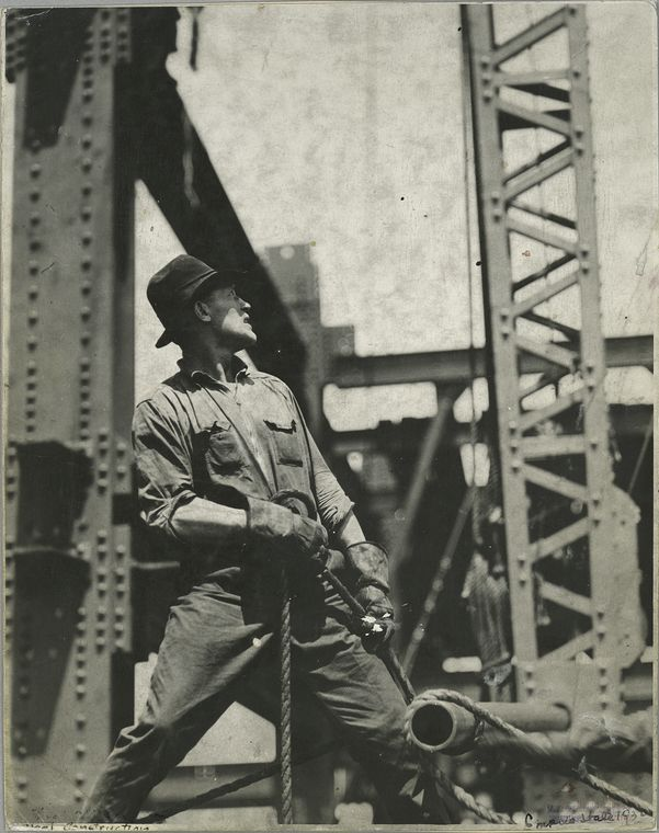 worker pulling on a rope looking upwards