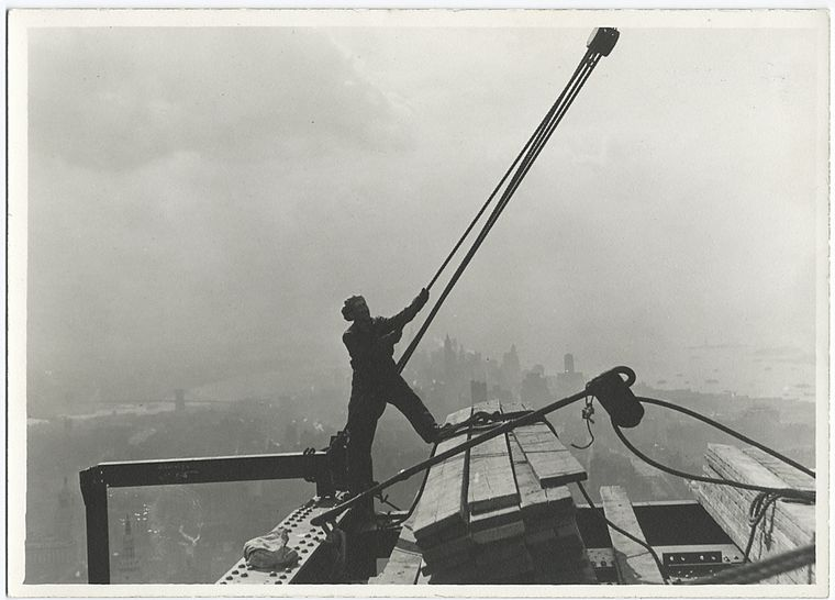 construction worker manoeuvring rope and pulley high up city in backdrop