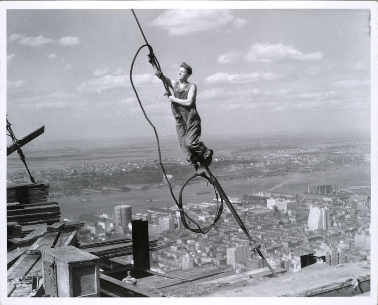 high up on a wire building the empire state building 1931 new york city visible in background