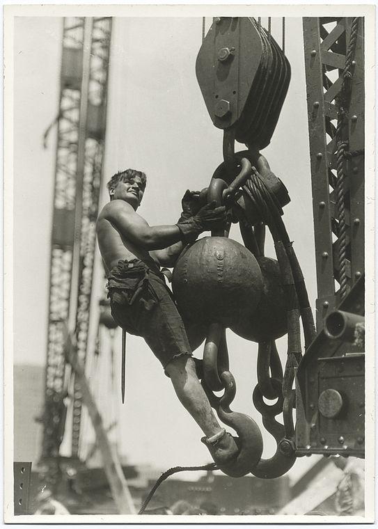 a worker riding on a massive crane hook