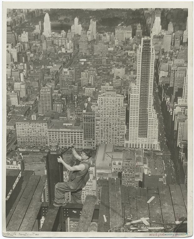 worker on edge of platform of empire state building 1931 new york city aerial clear in background