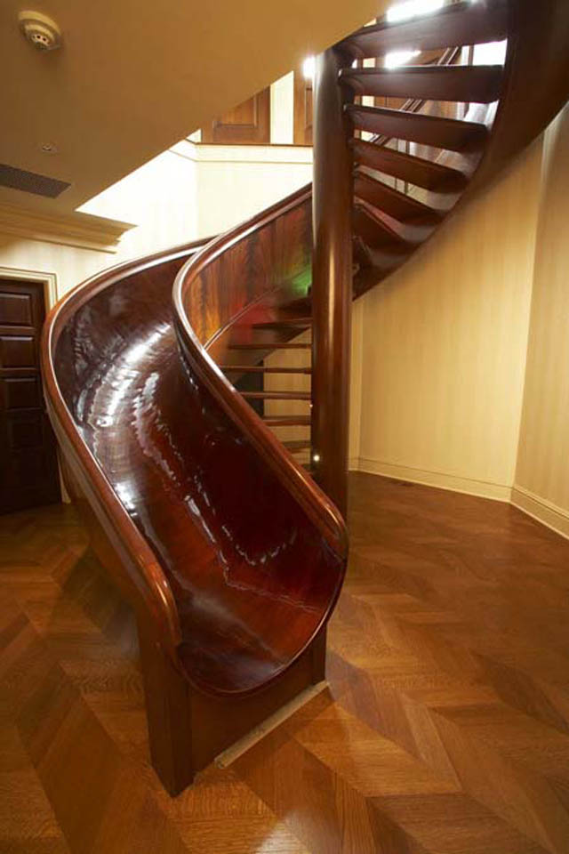 indoor spiral staircase made of wood with a slide integrated into it
