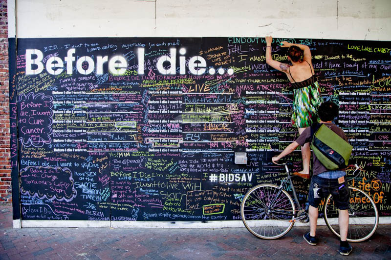 standing on a bike to reach top of before i die footprint to write her submission