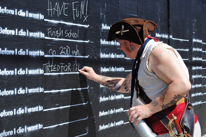 man in pirate hat writing on before i die wall