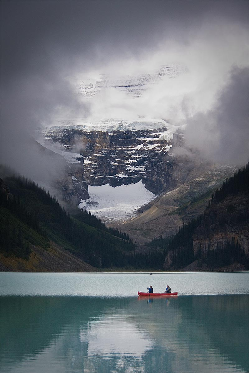 break in the clouds as two people in canoe see a spec of sun hiting the victoria glacier above a glacial lake in lake louise banff alberta canada