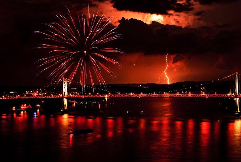 a bolt of lightning lights up the sky at the exact same moment as a large fireworks display