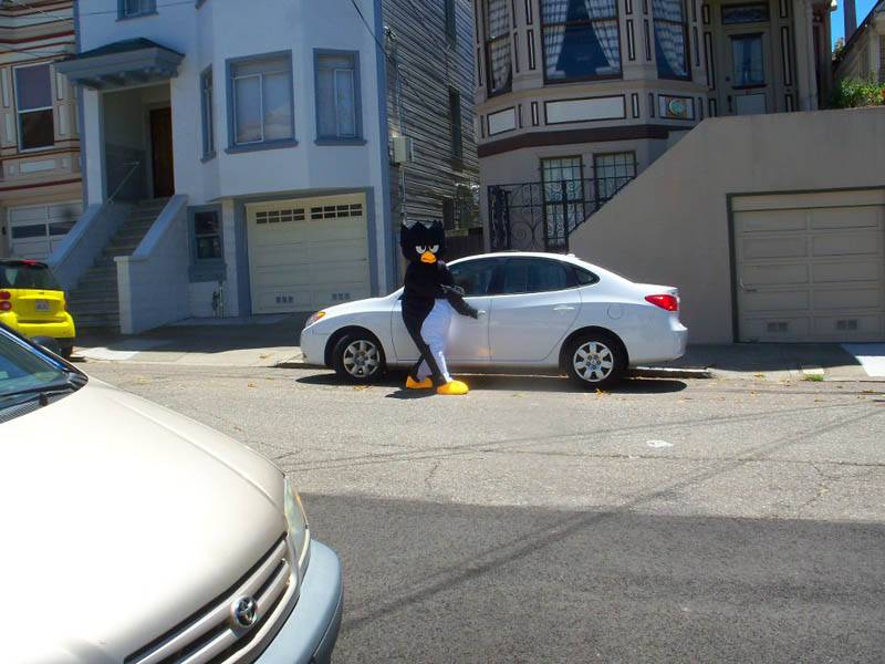 guy in angry bird costume getting into his car staring at person across street taking a picture