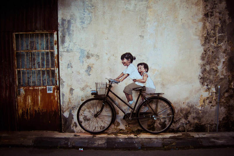 artwork of girl and boy on a wall with a real bicycle placed in front that looks like they are riding it