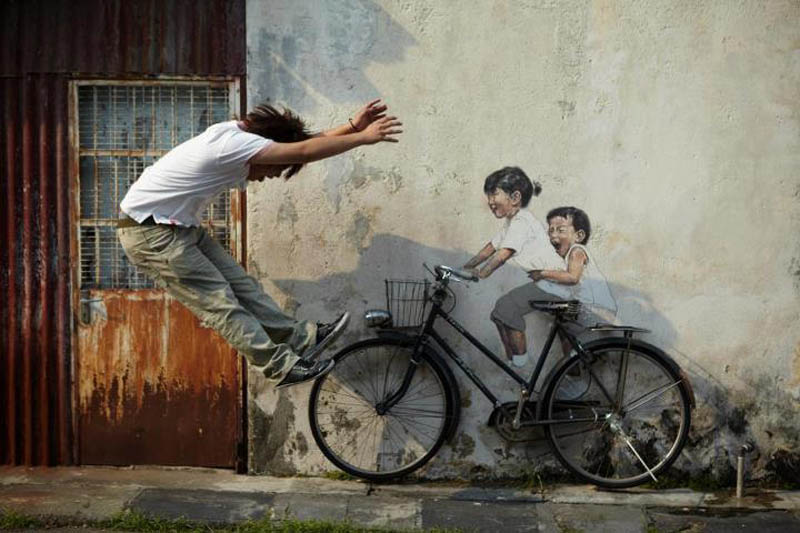 intearctive street art painted kids on wall riding real bike armenian street george town malaysia ernest zacharevic 2 This Interactive Street Art in Malaysia is Brilliant
