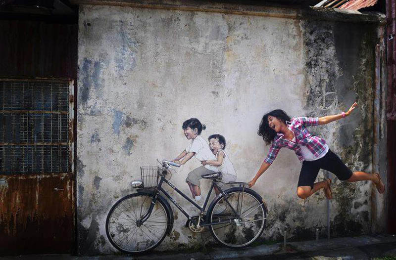 intearctive street art painted kids on wall riding real bike armenian street george town malaysia ernest zacharevic 8 How To Climb a 3 Story House Without Leaving the Ground