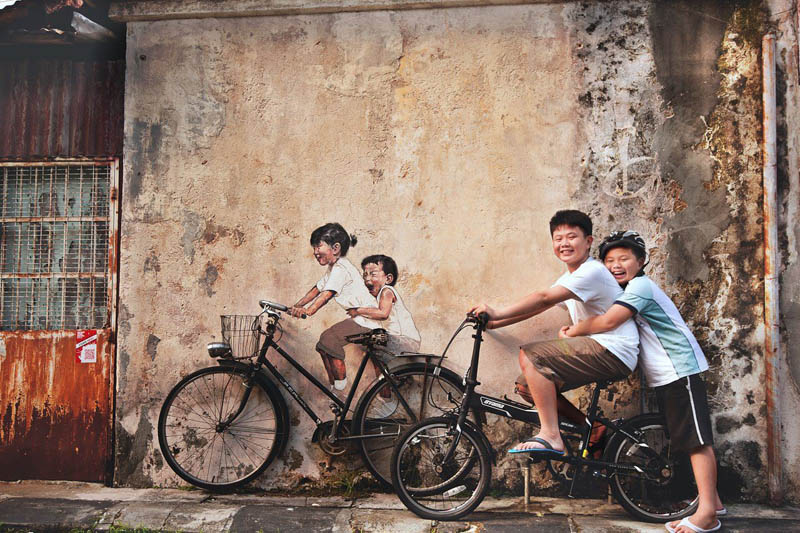 interactive street art painted kids on wall riding real bike armenian street george town malaysia ernest zacharevic 1 This Interactive Street Art in Malaysia is Brilliant