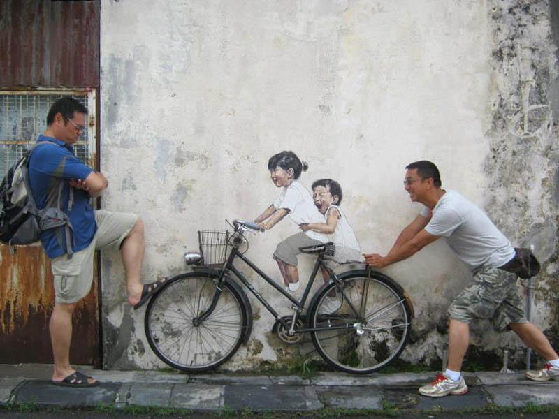 interactive street art painted kids on wall riding real bike armenian street george town malaysia ernest zacharevic 4 This Interactive Street Art in Malaysia is Brilliant