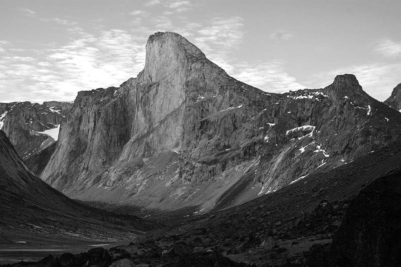 Mount thor or thor peak has the greatest purely vertical drop in the entire world. a wide angle shot of the mountain black and white
