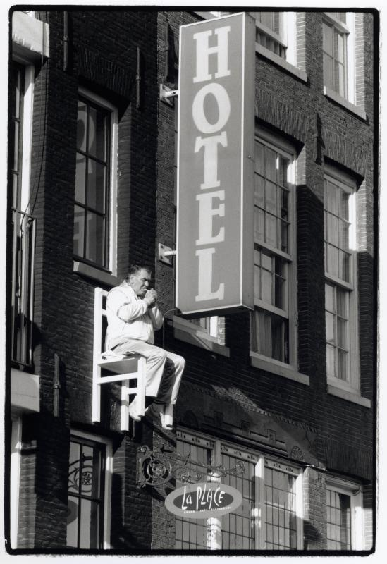 old man lighting a cigarette sitting in a chair high above the street in montreal
