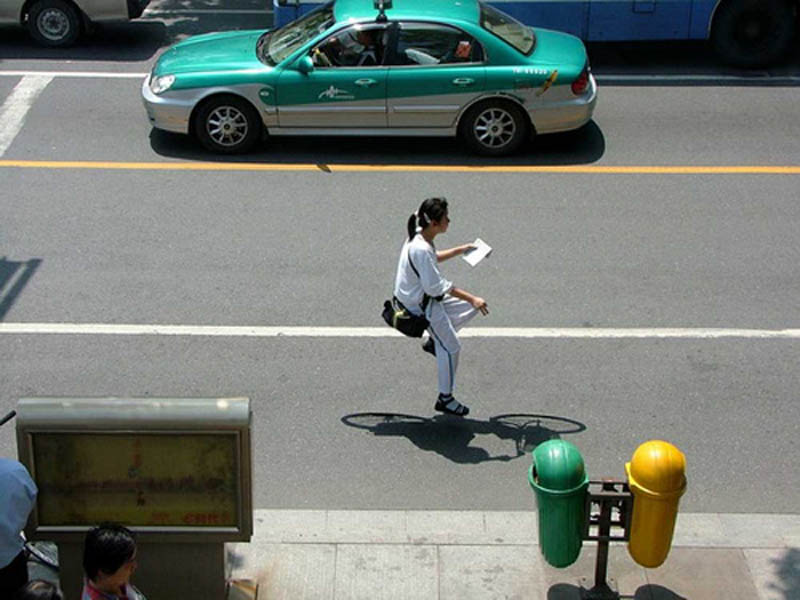 woman on street riding an invisible bike