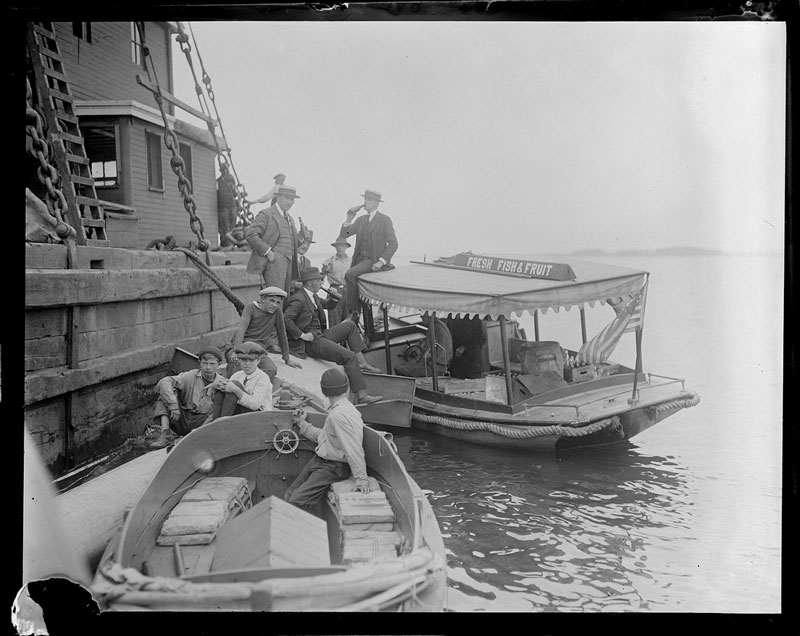 Boat with sign Fresh Fish and Fruit delivers bottled drinks to men on pier (possibly Prohibition selling illegal alcohol)