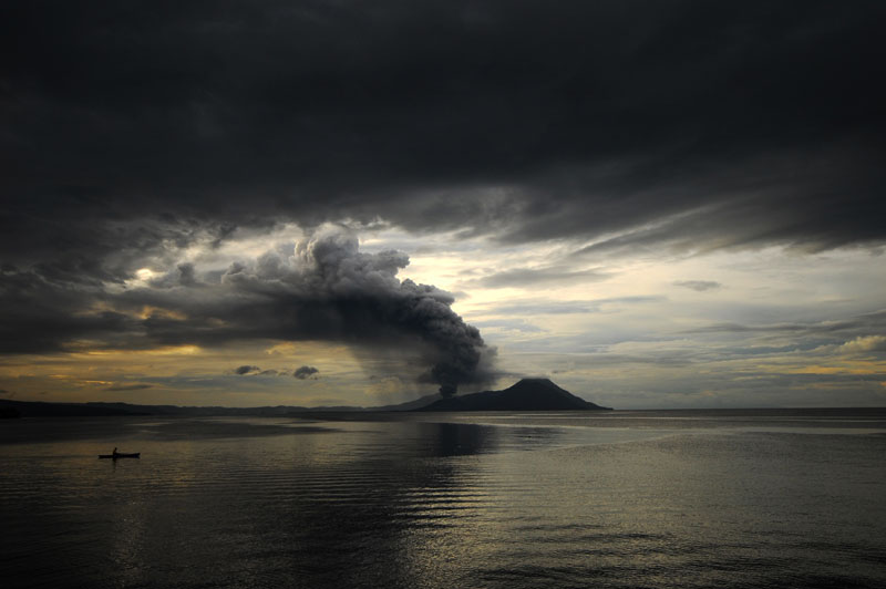 lone fisherman with volcano behind ash plume Picture of the Day: The Lone Fisherman