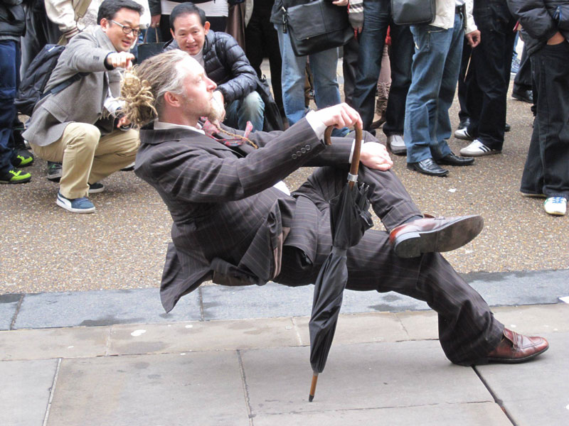 man in suit sitting leaning back on street illusion The Shirk Report   Volume 188