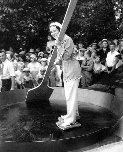 Woman-with-slabs-of-bacon-tied-to-her-feet-standing-in-a-giant-skillet-holding-an-enormous-wooden-spatula-Chehalis,-Washington