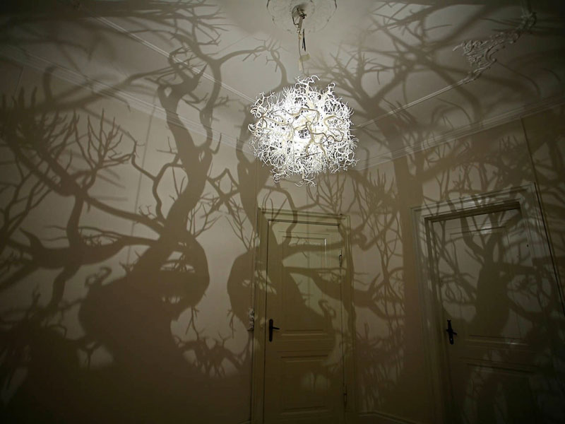 chandelier projects shadow forest on walls hilden and diaz 1 Old Sea Mines Repurposed Into Furniture