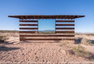 A Transparent Cabin of Wood and Mirrors on a Desert Landscape