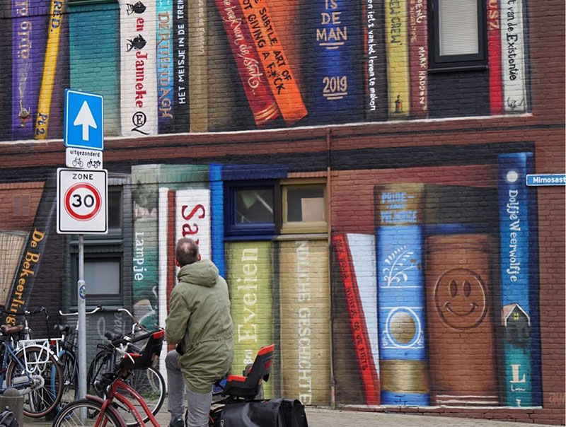 giant 3d bookshelf street art by jan is de man and deef feed 3 Dutch Artists Paint Giant 3D Bookshelf of Neighborhoods Favorite Books