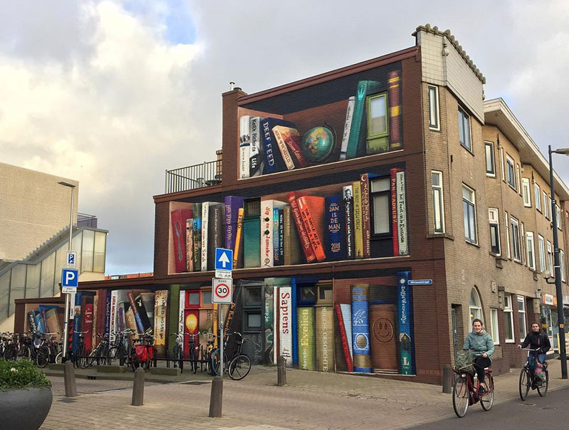giant 3d bookshelf street art by jan is de man and deef feed 4 Dutch Artists Paint Giant 3D Bookshelf of Neighborhoods Favorite Books
