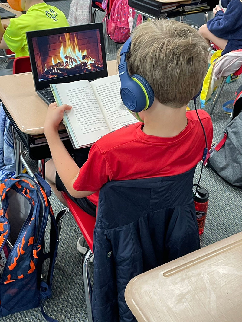 student puts on fireplace channel on computer while reading at desk This Kid Made His Own Cozy Atmosphere During Reading Time